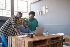 Усмехаясь африканские коллеги используя компьтер-книжку на столе офиса Стоковое Фото