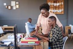 Усмехаясь африканские коллеги офиса говоря совместно над компьютером Стоковое Изображение