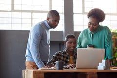 Усмехаясь африканские предприниматели работая на компьтер-книжке в офисе Стоковые Изображения RF