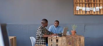 Усмехаясь африканские сотрудники говоря совместно в современном офисе Стоковые Изображения