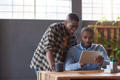 Усмехаясь африканские сотрудники используя цифровую таблетку в офисе Стоковые Изображения RF