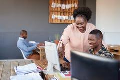 Усмехаясь африканские сотрудники работая на компьютере в офисе Стоковая Фотография