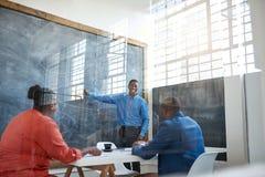 Усмехаясь африканский бизнесмен давая представление в офисе Стоковые Изображения