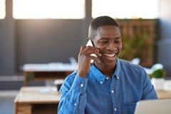 Усмехаясь африканский бизнесмен говоря на мобильном телефоне в офисе Стоковое Фото