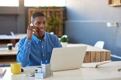 Усмехаясь африканский бизнесмен крепко на работе в современном офисе Стоковое Изображение