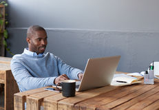 Усмехаясь африканский бизнесмен работая на компьтер-книжке на его столе Стоковое фото RF