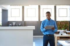 Усмехаясь африканский бизнесмен работая на таблетке в офисе Стоковая Фотография