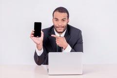 Усмехаясь африканский бизнесмен сидя на таблице и указывая на Стоковые Изображения RF