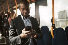 Усмехаясь африканский бизнесмен слушая к музыке во время его mornin стоковое изображение