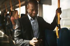 Усмехаясь африканский бизнесмен стоя на шине слушая к музыке стоковое фото rf