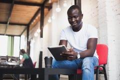 Усмехаясь африканский человек используя таблетку для видео- переговора в современном офисе Стоковая Фотография RF