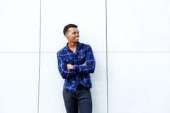 Усмехаясь африканский человек стоя с оружиями пересек против стены стоковая фотография