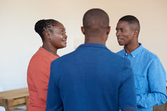 3 усмехаясь африканских коллеги офиса говоря совместно на работе Стоковое Изображение