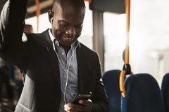 Усмехаясь африканское катание бизнесмена на шине слушая к музыке стоковое фото