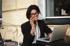 Усмехаясь Афро-американская девушка в стеклах сидя на таблице кафа и работая на компьтер-книжке Милая дама с темное курчавым Стоковые Изображения RF