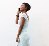 Усмехаясь Афро-американская женщина говоря на мобильном телефоне Стоковые Изображения RF