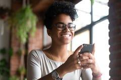 Усмехаясь Афро-американская женщина используя телефон, получает хорошее сообщение стоковая фотография rf