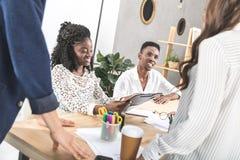 усмехаясь Афро-американские коллеги на деловой встрече на рабочем месте Стоковые Изображения