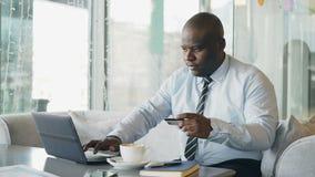 Усмехаясь Афро-американский бизнесмен в официально одеждах оплачивая онлайн счет используя его кредитную карточку и компьтер-книж сток-видео