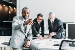 усмехаясь Афро-американский указывать бизнесмена отсутствующий пока коллеги дела обсуждая работу Стоковые Фото