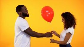 Усмехаясь афро-американский человек представляя воздушный шар к милой женщине, подарку на день рождения, дате стоковое изображение rf