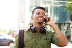 Усмехаясь Афро-американский человек говоря на мобильном телефоне в городе стоковое фото