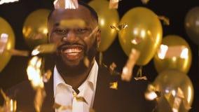 Усмехаясь Афро-американское положение человека под падая confetti, украшениями партии сток-видео