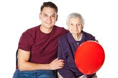 Усмехаясь бабушка и внук с красным воздушным шаром Стоковое Изображение