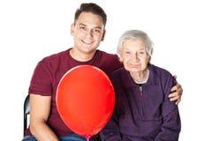 Усмехаясь бабушка и внук с красным воздушным шаром Стоковые Фото