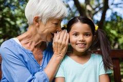 Усмехаясь бабушка шепча в ушах девушки Стоковые Изображения