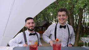 Усмехаясь бармены за подачами коктеилем бара, барменом делая холодное питье в стекле, бармене украшают коктеили акции видеоматериалы