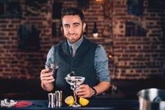 Усмехаясь бармен и профессионал, смотрящ камеру и подготавливать коктеиль Стоковое Изображение