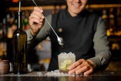 Усмехаясь бармен шевеля свежее mojito в стекле коктеиля Стоковые Фото