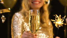 Усмехаясь белокурая дама держа стекло шампанского и света Бенгалии, падать confetti акции видеоматериалы