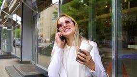 Усмехаясь белокурая женатая женщина говоря на мобильном телефоне на улице города сток-видео