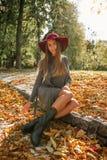 Усмехаясь белокурая женщина в сером knit одевает и красная шляпа представляя на th Стоковое Изображение RF