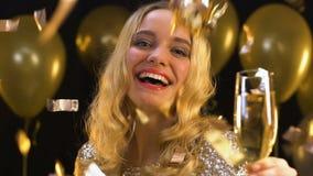 Усмехаясь белокурая женщина с положением шампанского стеклянным под падая confetti, партией сток-видео