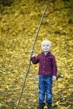 Усмехаясь белокурый мальчик с ручкой в его руке осенняя пуща стоковое фото