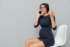 Усмехаясь беременная бизнес-леди говоря телефоном Стоковые Фото