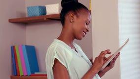 Усмехаясь беременная женщина используя ПК таблетки сток-видео