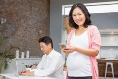 Усмехаясь беременная женщина используя smartphone Стоковое Фото