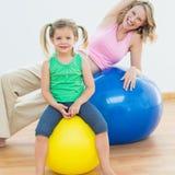 Усмехаясь беременная женщина работая на шарике тренировки с молодой дочерью Стоковые Изображения RF