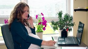Усмехаясь беременная женщина секретарши делая примечания назначения пока говорящ на телефоне акции видеоматериалы