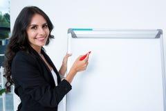 усмехаясь беременное сочинительство коммерсантки на whiteboard с красным цветом Стоковое фото RF