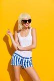 Усмехаясь белокурая девушка в черных солнечных очках Стоковое Фото