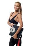 Усмехаясь белокурая женщина держа масштаб веса Фитнес Стоковое Изображение