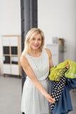 Усмехаясь белокурая женщина показывая ей дополнительные одежды Стоковое Изображение RF