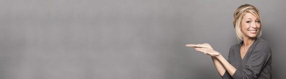 Усмехаясь белокурая женщина показывая пустой космос левой стороны стоковая фотография rf