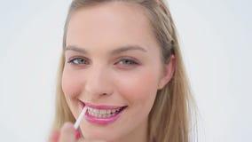 Усмехаясь белокурая женщина прикладывая лоск губы на ее губах сток-видео