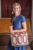 Усмехаясь белокурая женщина с сливк и сделанным по образцу красным цветом портмонем Стоковое Изображение